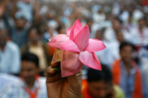 File: A supporter of India's main opposition Bharatiya Janata Party (BJP) holds his party's lotus symbol during a felicitation ceremony outside the party office in the western Indian city of Ahmedabad December 20, 2012.