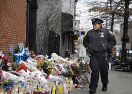 A New York City police officer looks over a makeshift memorial near the site where fellow officers Rafael Ramos and Wenjian Liu were murdered in the Brooklyn borough of New York, Monday, Dec. 22, 2014.