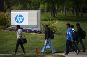 Pedestrians walk by a sign outside of the Hewlett-Packard headquarters on May 23, 2014 in Palo Alto, California.  HP announced on Thursday that it plans to lay off an additional 11,000 to 16,000 employees over its previously scheduled mass layoffs of 34,000.