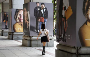 A woman walks in front of advertisements for Gucci, a luxury retail unit of Kering SA, in Tokyo, Japan, on Thursday, May 29, 2014. Japan's industrial production and household spending fell more than forecast and inflation surged to a 23-year high on a tax rise that is pinching consumers who have seen limited wage gains. Photographer: Tomohiro Ohsumi/Bloomberg
