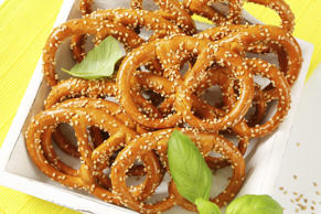 heap of spelt pretzels with sesame seeds on white wooden kitchen tray
