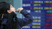 A girl drinks tea in front of an electronic stock board of a securities firm in Tokyo, Monday, Feb. 16, 2015. Tokyo's Nikkei 225 was up 91.41 points from Friday at 18,004.77 as Asian stock markets mostly rose Monday after Japan emerged from recession last quarter.