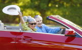 caucasian senior couple on their 70s riding on their red convertible