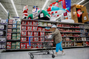 A woman pushes a shopping cart past Christmas decorations displayed for sale at a WalMart Store in Los Angeles, California.