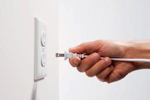 Man unplugs a device from an electrical outlet.