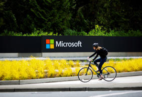 A woman rides a bicycle past a Microsoft Corp. sign on the company's main campus in Redmond, Washington, U.S., on Wednesday, July 17, 2014. Microsoft Corp. said it will eliminate as many as 18,000 jobs, the largest round of cuts in its history, as Chief Executive Officer Satya Nadella integrates Nokia Oyj's handset unit and slims down the software maker.