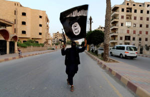Islamic State militant with ISIS flag in Raqqa, Syria. June 29, 2014.