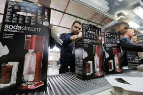 Employees pack boxes of the SodaStream product at the factory in the West Bank Jewish settlement of Maale Adumim January 28, 2014. Appliance maker SodaStream International Ltd scored big in nabbing A-list actress Scarlett Johansson as its global brand ambassador in time for this year's Super Bowl advertising bonanza. But the limelight can be harsh. While the multi-million dollar deal may have increased brand awareness, it also strengthened calls for a boycott of the Israel-based company, whose main factory lies in a Jewish settlement deep in the occupied West Bank. Picture taken January 28, 2014. To match ISRAEL-PALESTINIANS/SCARLETTJOHANSSON REUTERS/Ammar Awad (WEST BANK - Tags: POLITICS ENTERTAINMENT BUSINESS SPORT FOOTBALL)