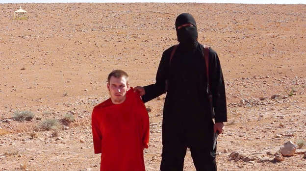 """American hostage Peter Kassig is paraded in front of the camera in an orange boiler suit in a video released on the internet showing the beheading of British hostage Alan Henning, by a British ISIL terrorist known as """"Jihadi John."""""""