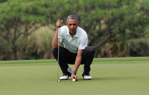 President Barack Obama lines up his ball as he and Malaysia's Prime Minister Najib Razak play on the 18th green at the Clipper Golf course on Marine Corps Base Hawaii during Obama's Christmas holiday vacation in Kaneohe, Hawaii, December 24, 2014.