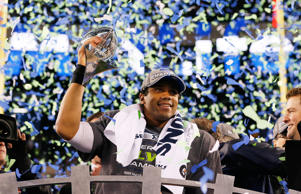 Quarterback Russell Wilson #3 of the Seattle Seahawks celebrates with the Vince Lombardi Trophy after their 43-8 victory over the Denver Broncos during Super Bowl XLVIII at MetLife Stadium on February 2, 2014 in East Rutherford, New Jersey.