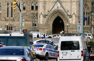 Police officers guard Parliament Hill following a shooting incident in Ottawa October 22, 2014.  A Canadian soldier was shot at the Canadian War Memorial and a shooter was seen running towards the nearby parliament buildings, where more shots were fired, according to media and eyewitness reports.