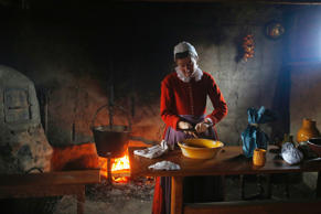 A woman playing the role of Bridget Fuller scrapes cinnamon into a bowl to make pancakes in a home at Plimoth Plantation in Plymouth, Massachusetts November 24, 2014. Plimouth Plantation is a living museum portraying the life of the Native Americans and the English colonists.