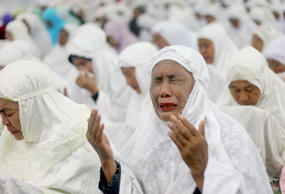 An Acehnese woman weeps during a prayer for the victims of Indian Ocean tsunami ahead of its 10th anniversary at Baiturrahman Grand Mosque in Banda Aceh, Aceh province, Indonesia, Thursday, Dec. 25, 2014. Some 230,000 people were killed in the tsunami set off by a magnitude 9.1 earthquake on Dec. 26, 2004, most of them in Aceh.