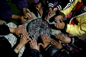 In this Dec. 10, 2014 photo, children from Yazidi families displaced by Islamic State group militants warm their hands over hot coals in a partially constructed building in Dohuk, northern Iraq.
