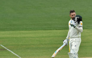 Australia's batsman Michael Clarke kisses his helmet as he celebrates his century on the second day of the first Test cricket match between Australia and India at the Adelaide Oval on December 10, 2014.