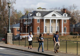 In this, Nov. 24, 2014, file photo, University of Virginia students walk to campus past the Phi Kappa Psi fraternity house at the University of Virginia in Charlottesville, Va.