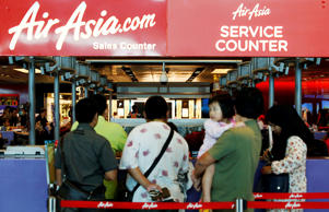 People queue at an AirAsia counter at Changi Airport in Singapore December 28, 2014. Indonesia's Transport Ministry official Hadi Mustofa said an AirAsia aircraft, flight number QZ 8501from Indonesian city of Surabaya to Singapore, lost contact with the Jakarta air traffic control tower on Sunday at 6:17 a.m local time. (2317 GMT). The Airbus 320-200 had 155 passengers and crew on board, another Indonesian Transport official said.