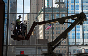 A contractor stands in a cherry picker while finishing construction on the 4 World Trade Center building, managed by Silverstein Properties Inc., in New York, U.S., on Wednesday, Sept. 25, 2013. Real estate developer Larry Silverstein can't recoup any of the $1.2 billion recovered by World Trade Center insurers in settlements with airlines and airport security companies over the Sept. 11, 2001, terrorist attack that destroyed the office complex, a judge ruled. Craig Warga/Bloomberg