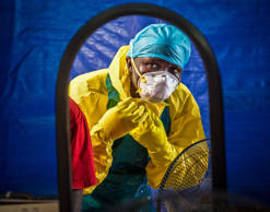 In this Thursday, Oct. 16, 2014 file photo, a healthcare worker dons protective gear before entering an Ebola treatment center in the west of Freetown, Sierra Leone. Michael Duff/AP