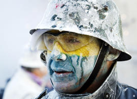 "A reveler, dressed in a mock military uniform, takes part in the battle of ""Enfarinats"", a flour fight, in the town of Ibi, south-eastern Spain, on December 28, 2014. Ibi's citizens annually celebrate the Els Enfarinats, a 200-year-old traditional festival part of the celebrations of the Day of the Innocents, with a battle using flour, eggs and firecrackers outside the city town hall."