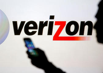Man checking his phone in front of a Verizon logo.