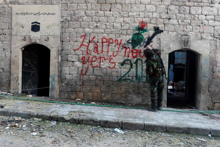 A Free Syrian Army fighter sprays graffiti on a wall prior to the new year in Aleppo, December 31, 2014.