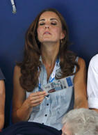 Catherine, Duchess of Cambridge fans herself with her Commonwealth Games accreditation as she watches the swimming at the Tollcross International Swimming Centre during the 20th Commonwealth Games in Glasgow, Scotland.