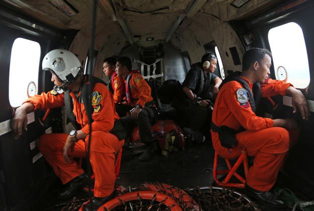 Crewmembers of an Indonesian Air Force NAS 332 Super Puma helicopter look out of the windows during a search operation for the victims and wreckage of AirAsia flight QZ 8501 over the Java Sea, Indonesia, January 5, 2015.