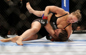 UFC women's bantamweight champion Ronda Rousey (top) punches Alexis Davis while controlling her body in their UFC women's bantamweight championship fight at UFC 175 inside the Mandalay Bay Events Center on July 5, 2014 in Las Vegas.