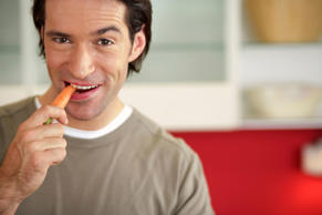 Man biting into a carrot