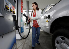 Lydia Holland replaces the gas nozzle after filling up at a gas station in Sacramento, Calif. .