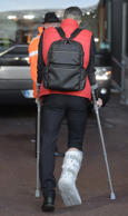 Manchester United's Robin van Persie leaves the Liberty Stadium on crutches with his foot in a protective plastic cast