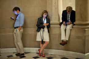 Reporters check their smartphones while waiting outside US House Speaker John Boehner's office at the US Capitol in Washington on September 30, 2013 as a possible government shutdown looms.