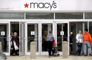 Shoppers go in and out the doors at a Macy's department store in Braintree, Mass., on April 29, 2014.