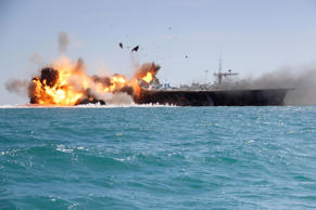 In this picture released by the Iranian Tasnim news agency, Feb. 25, 2015, a replica of a U.S. aircraft carrier is exploded by the Revolutionary Guard's speedboats during large-scale naval drills near the entrance of the Persian Gulf, Iran.