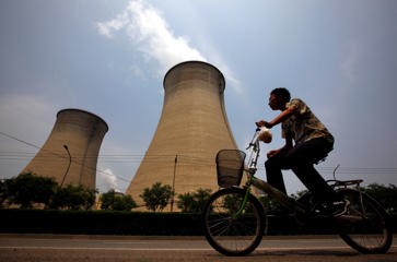 A man rides his bicycle past the cooling tower and chimneys from a coal-burning power station in Beijing, China.