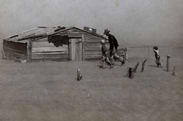 Photograph of a farmer and son walking in the face of a dust storm in Cimarron County, Oklahoma taken in April, 1936.