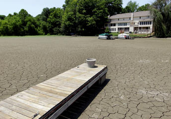 A dock extends into a dry cove that is 3.5 feet from normal levels at Morse Reservoir in Noblesville, Ind., on July 5, 2012.