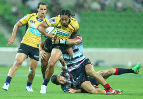 Joe Tomane of the Brumbies breaks through a tackle during the round three Super Rugby match between the Rebels and the Brumbies.