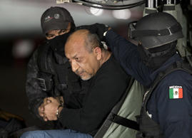 "Federal police escort who they identify as Servando ""La Tuta"" Gomez,"" leader of the Knights Templar cartel, as he sits inside helicopter at a Federal hanger in Mexico City, Feb. 27, 2015."