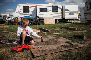 A boy plays with toy motorcycles in a trailer park on July 29, 2013 in Watford City, North Dakota.