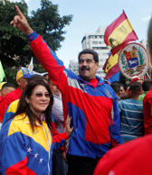 Venezuela's President Nicolas Maduro, center, greets supporters next to his wife, Cilia Flores, during a rally to commemorate the 26th anniversary of the social uprising known as 'Caracazo', which late President Hugo Chavez said marked the start of his revolution, in Caracas in this February 28, 2015 picture provided by Miraflores Palace.