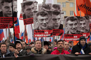 People march in memory of opposition leader Boris Nemtsov who was gunned down Feb. 27, 2015 near the Kremlin, with portraits of him and words reading 'he died for the freedom to Russia, heroes never die!' in Moscow, Russia, March 1, 2015.