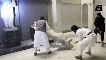In this image made from video posted on a social media account affiliated with the Islamic State group, Feb. 26, 2015, which has been verified and is consistent with other AP reporting, militants take sledgehammers to an ancient artifact in the Ninevah Museum in Mosul, Iraq.