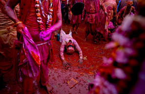 <p>An Indian Hindu devotee from Barsana village prostrates amid colors as he prays at the Nandagram temple, famous for Lord Krishna and his brother Balram, during Lathmar holi festival, in Nandgaon, India, Feb. 28, 2015. </p>