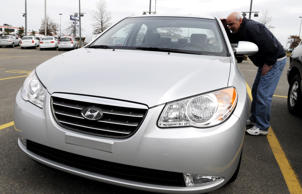 In this file photo, Mike Sieber, of North Attleboro, Mass., looks at a silver Hyundai Elantra in Lynn, Mass.