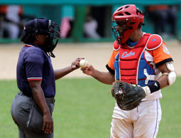 Cuban umpire Yanet Moreno (L) talks to Villa Clara's catcher Yulexis la Rosa during a baseball game between Villa Clara and Camaguey in Villa Clara province, Cuba, on October 18, 2014.