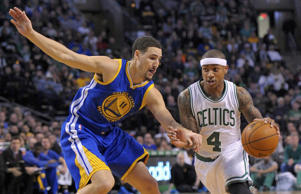 Boston Celtics guard Isaiah Thomas (4) controls the ball while being defended by Golden State Warriors guard Klay Thompson (11) during the first half March 1 in Boston.
