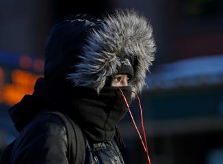 A pedestrian is bundled up against the frigid weather on Friday, Feb. 13, 2015, in Albany, N.Y. Hundreds of schools across upstate New York closed or delayed the start of classes because of below-zero temperatures and wind chill as low as minus-40 in some areas.